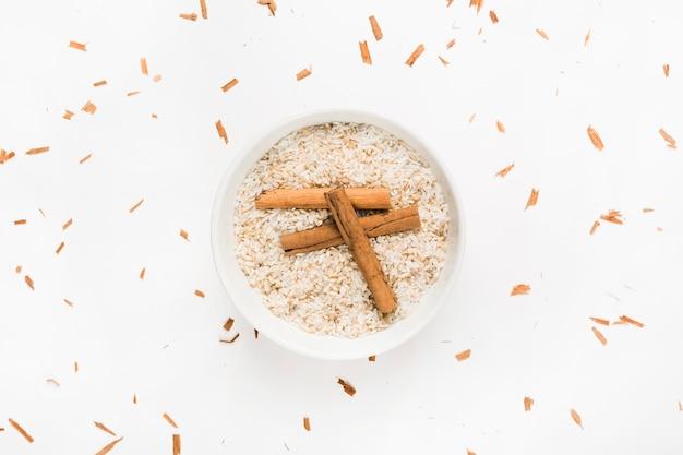 Paus de canela na tigela de arroz cru sobre fundo branco Foto gratuita