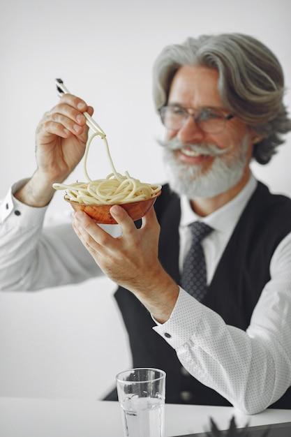 Pausa para o almoço. homem elegante no escritório. empresário de camisa branca. o homem come macarrão. Foto gratuita