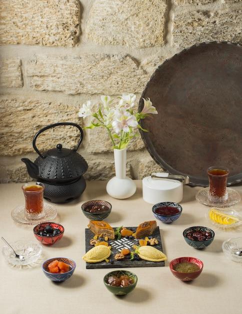 Pausa para o chá com chaleira preta, copos de chá e rendição doce Foto gratuita