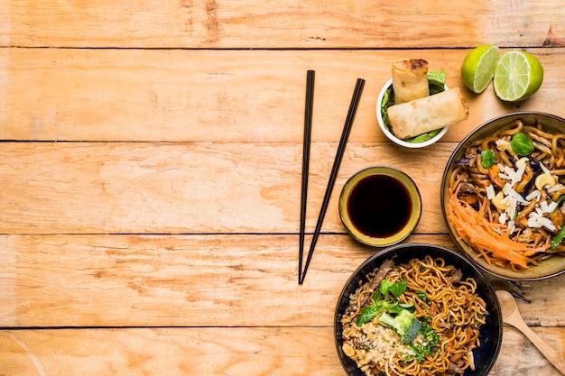 Pauzinhos com rolinhos primavera; macarrão e molhos com pauzinhos na mesa de madeira Foto gratuita