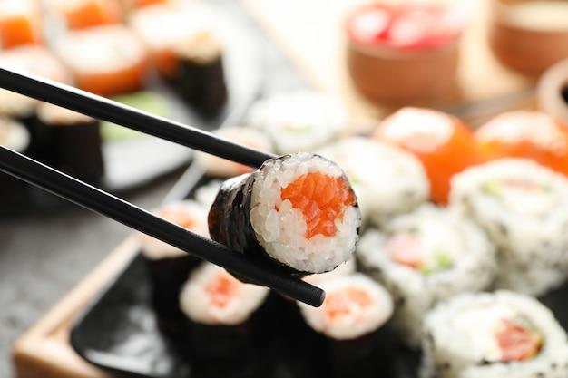Pauzinhos com rolo de sushi delicioso. comida japonesa Foto Premium