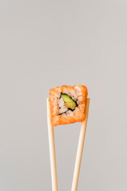 Pauzinhos com rolo de sushi Foto gratuita