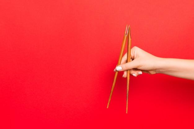Pauzinhos de madeira holded com mãos femininas sobre fundo vermelho. pronto para comer s com espaço vazio Foto Premium