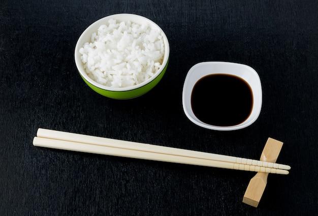 Pauzinhos de sushi japonês sobre tigela de molho de soja, arroz em fundo preto Foto Premium
