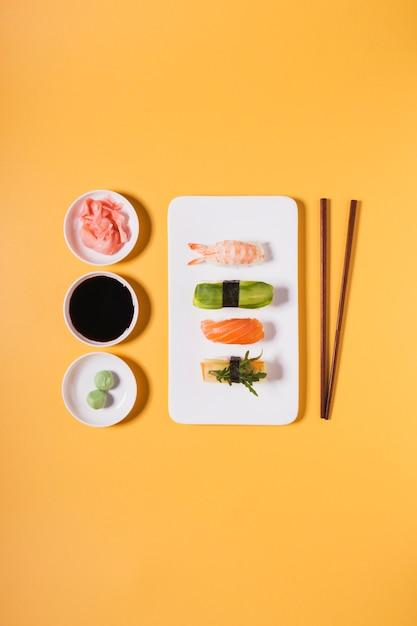 Pauzinhos e condimentos perto de sushi variado Foto gratuita