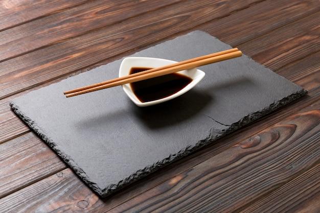 Pauzinhos e molho de soja na placa de pedra preta Foto Premium