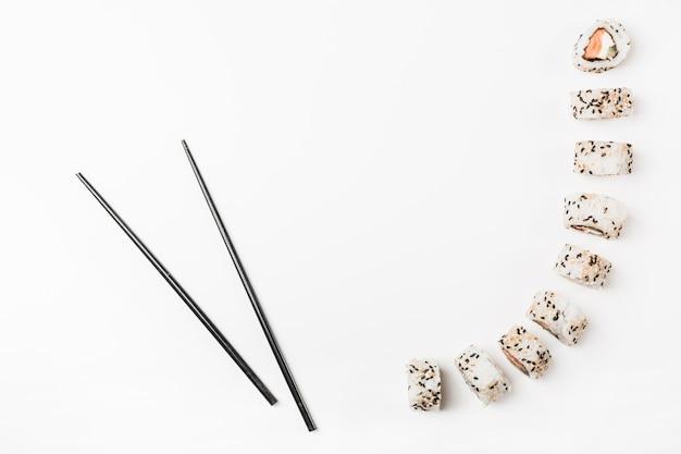 Pauzinhos pretos com rolos de sushi no fundo branco Foto gratuita
