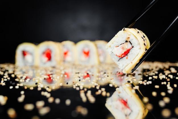Pauzinhos segurando o rolo feito de nori, arroz marinado, philadelphia, queijo Foto gratuita