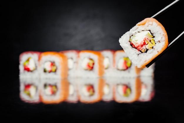 Pauzinhos segurando sushi roll filadélfia feitos de salmão, atum, pepino, nori Foto gratuita