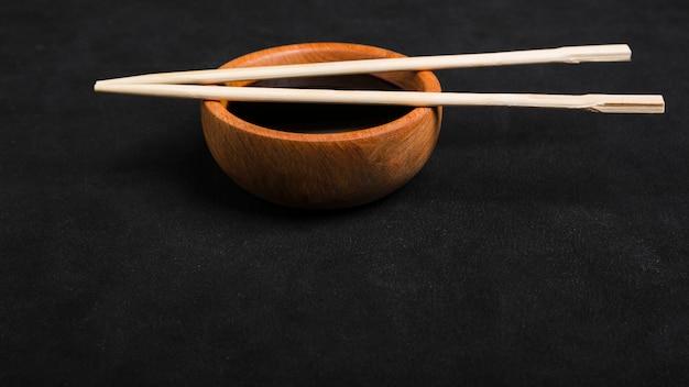 Pauzinhos sobre a tigela de madeira de molho de soja em pano de fundo preto Foto gratuita