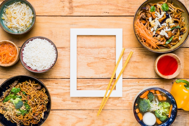 Pauzinhos sobre o quadro branco fronteira e comida tailandesa na mesa de madeira Foto gratuita