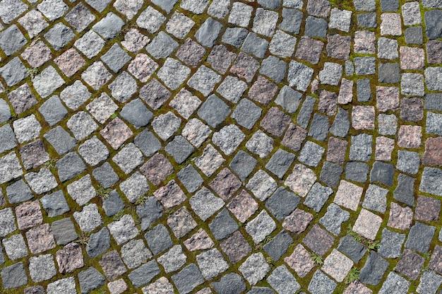 Pavimento em pedra de granito. textura de pavimento de estrada de calçada velha Foto Premium