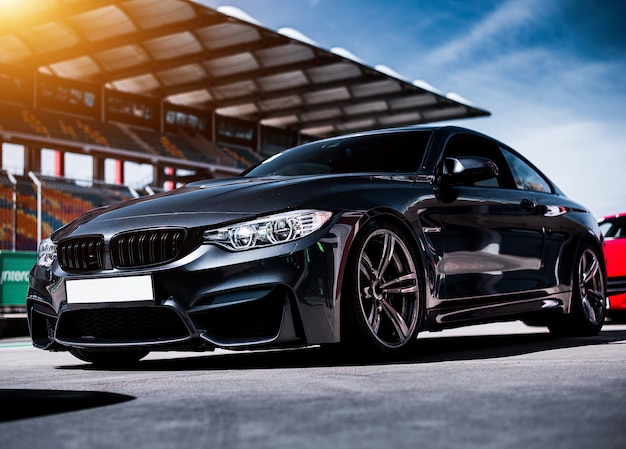Pé de carro sedan esporte de luxo preto sobre o traço de corrida Foto gratuita