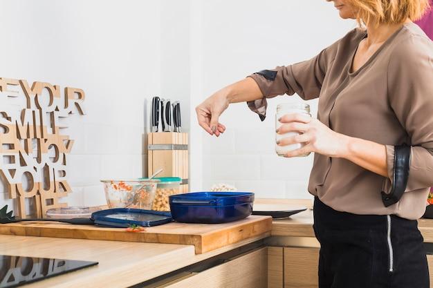 Pé feminino, em, cozinha, salting, alimento Foto gratuita