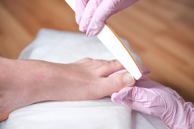 Pé feminino em processo de procedimento de pedicure em um close do salão de beleza. médico de podologia. tratamento de pés e unhas Foto Premium