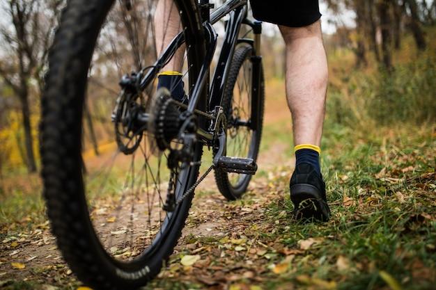 Pé no pedal da bicicleta no parque, verão ativo. fechar-se. Foto gratuita