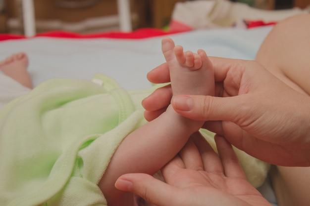 Pé o bebê dormindo nas mãos da mãe Foto Premium