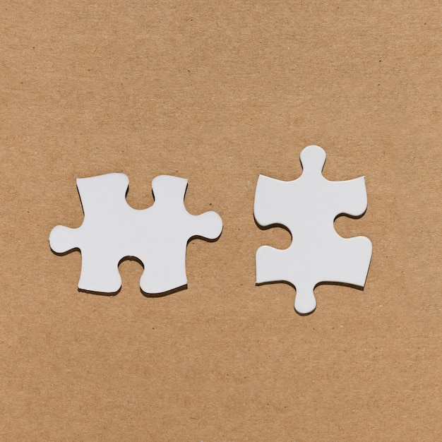 Peça de quebra-cabeça branca sobre papel marrom texturizado Foto gratuita