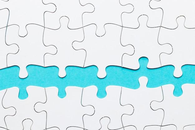Peça de quebra-cabeça contra no pano de fundo azul Foto gratuita