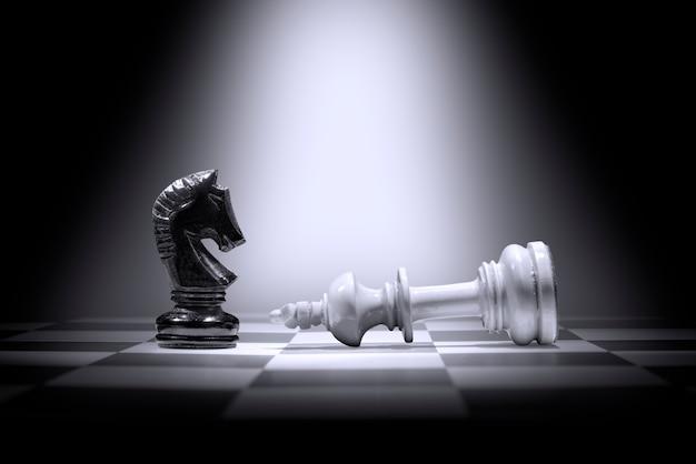 Peça de xadrez do rei branco derrotando por peça de xadrez de cavaleiro negro Foto Premium