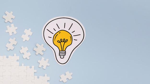 Peças de lâmpada e quebra-cabeça com espaço de cópia Foto gratuita