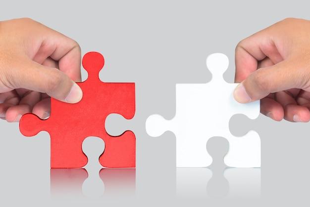 Peças de mão e quebra-cabeça em fundo branco Foto Premium