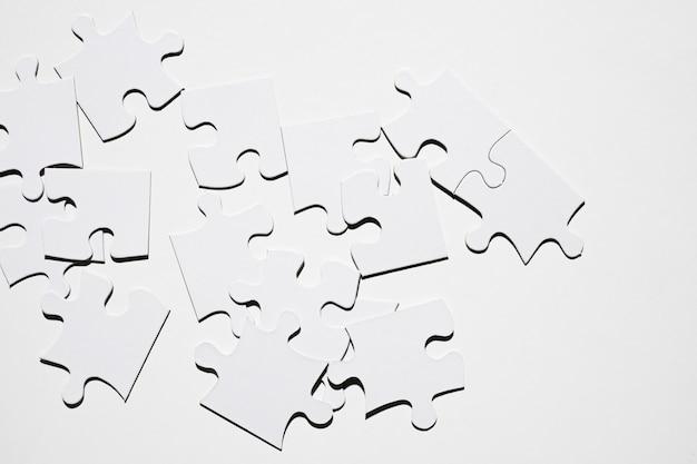 Peças de quebra-cabeça branca isoladas na superfície branca Foto gratuita