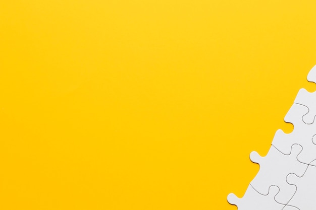 Peças de quebra-cabeça branca no canto do fundo amarelo Foto gratuita