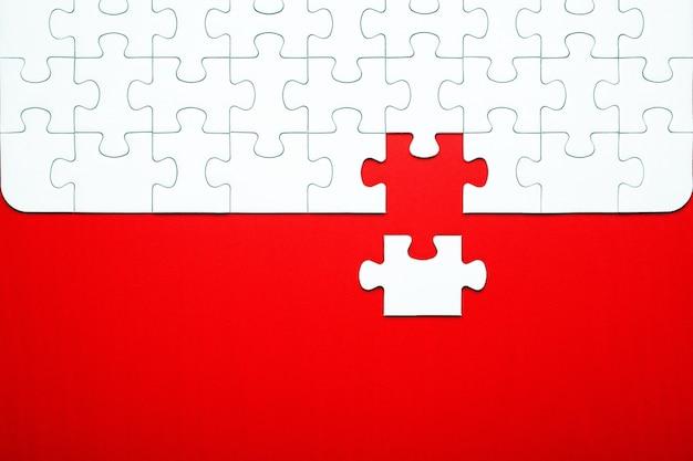 Peças de quebra-cabeça branca sobre um fundo vermelho separados Foto Premium