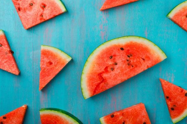 Peças dispersas da melancia no fundo azul, vista superior. Foto gratuita