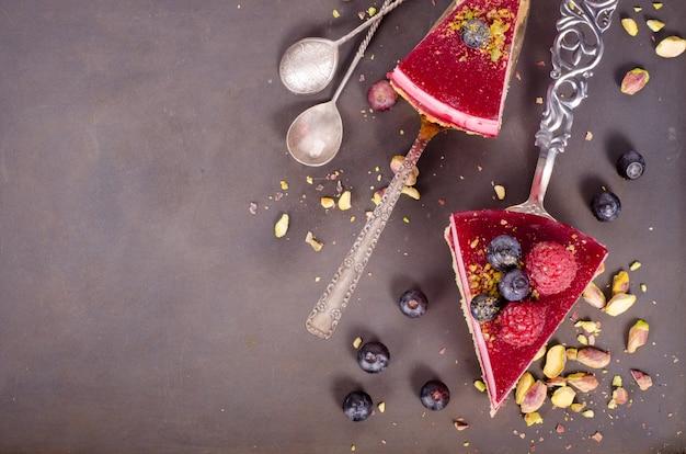 Pedaço de bolo de framboesa delicioso com framboesas frescas, mirtilo, groselhas e pistácios na pá Foto Premium