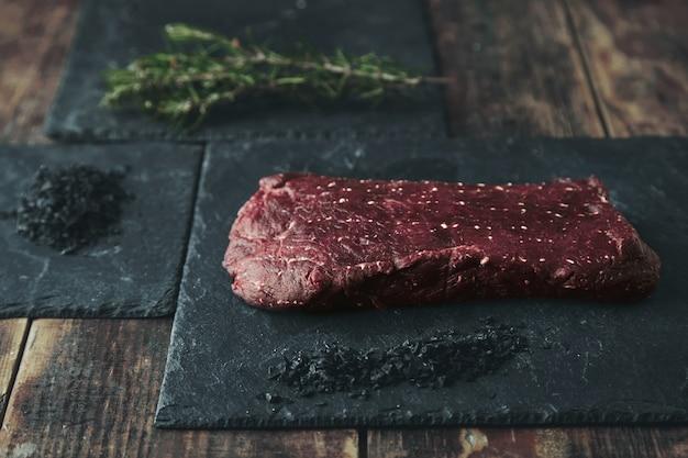 Pedaço de carne crua em uma almofada de pedra preta perto de sal vulcânico preto e erva e especiarias de alecrim Foto gratuita