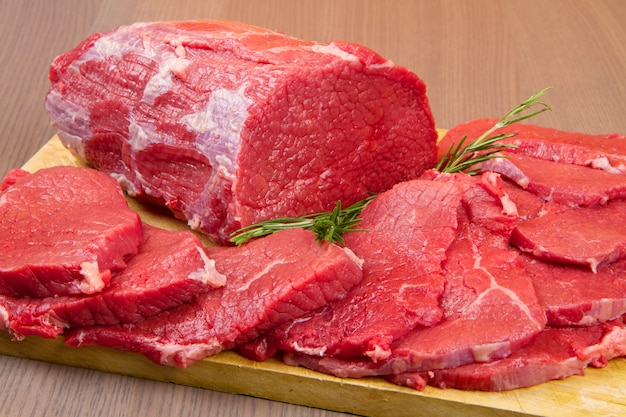 Pedaço de carne vermelha enorme e bife na mesa de madeira Foto Premium