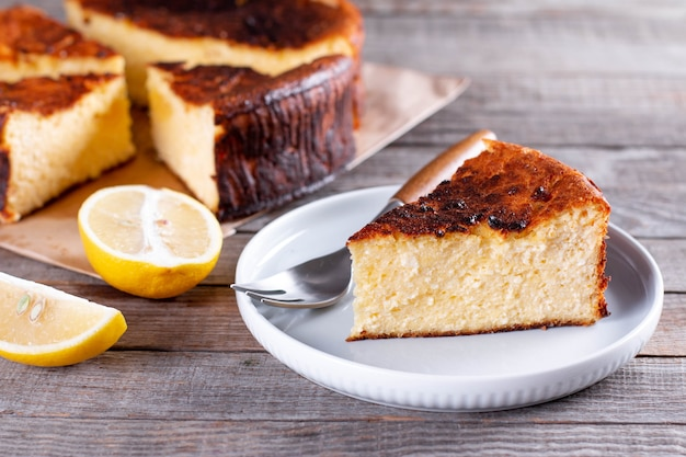 Pedaço de cheesecake basco de san sebastian no prato sobre uma mesa de madeira com limão e uma xícara de chá Foto Premium