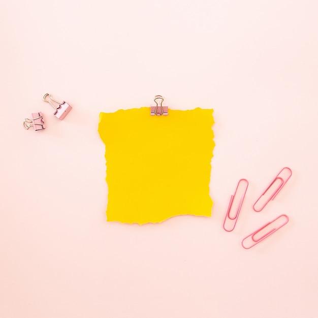 Pedaço de folha amarela sobre um fundo rosa Foto gratuita