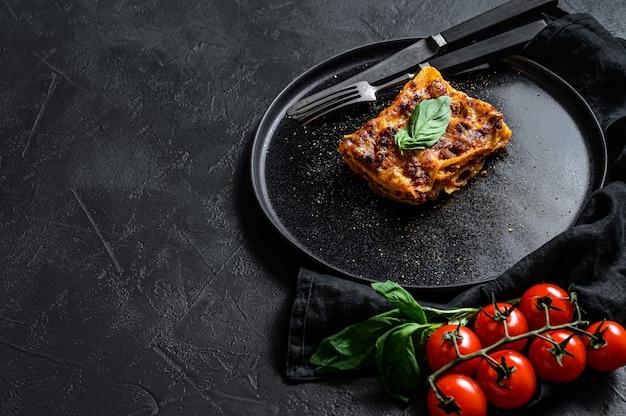 Pedaço de lasanha quente saborosa. comida italiana tradicional. espaço para texto Foto Premium