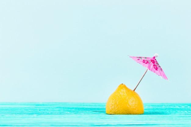 Pedaço de limão amarelo com guarda-chuva rosa no topo em fundo azul Foto gratuita