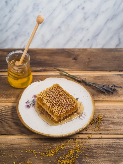 Pedaço de mel na placa branca de madeira com pólen de lavanda e abelha na mesa de madeira Foto gratuita