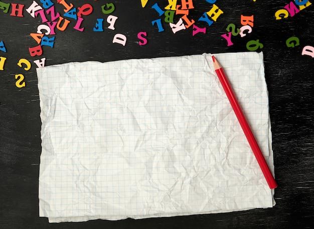 Pedaço de papel amassado de um caderno escolar em uma gaiola Foto Premium
