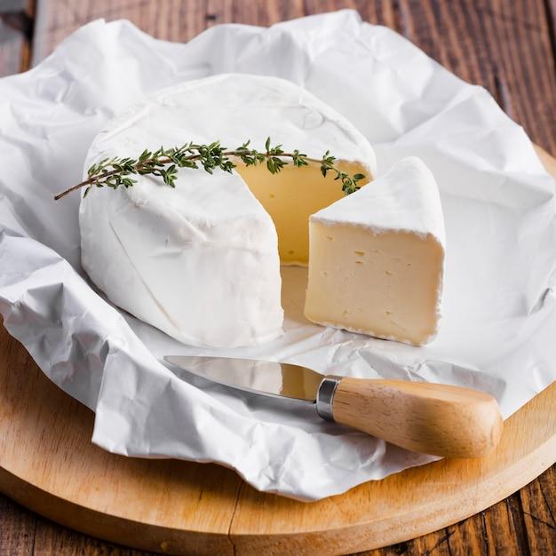 Pedaço de queijo com faca close-up Foto gratuita
