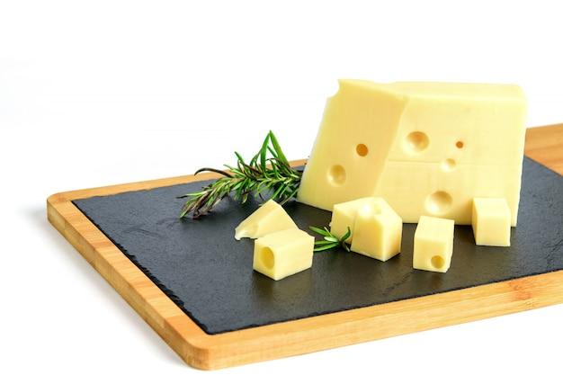 Pedaço de queijo emmental e alecrim no quadro de tapas preto. Foto Premium