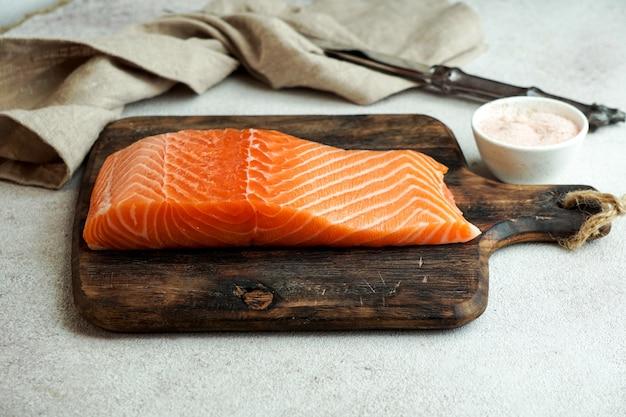 Pedaço de salmão fresco cru na tábua com sal Foto Premium