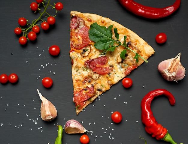 Pedaço triangular de pizza assada com cogumelos, linguiça defumada, tomate e queijo Foto Premium