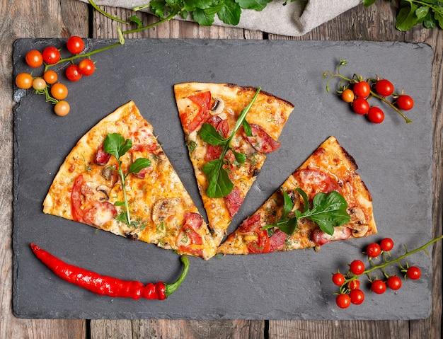 Pedaço triangular de pizza assada com cogumelos, linguiça defumada, tomate Foto Premium