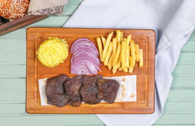 Pedaços de bife de carne com batatas fritas, cebola e arroz na placa de madeira. Foto gratuita