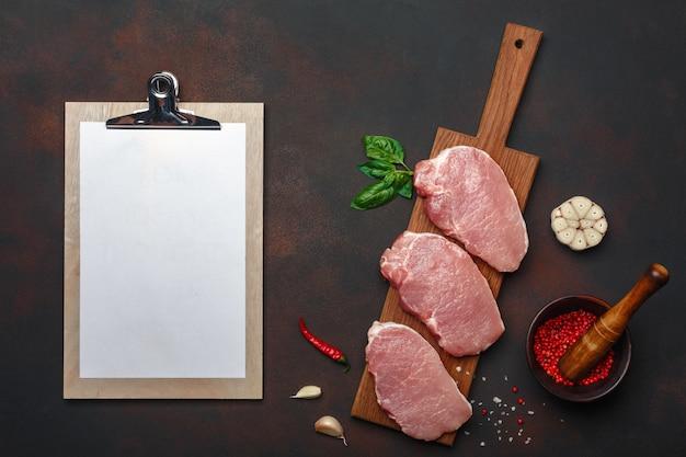 Pedaços de bife de carne de porco crua com manjericão, alho, pimenta, sal e especiaria argamassa e tablet na placa de corte e fundo marrom enferrujado com espaço para seu texto. Foto Premium