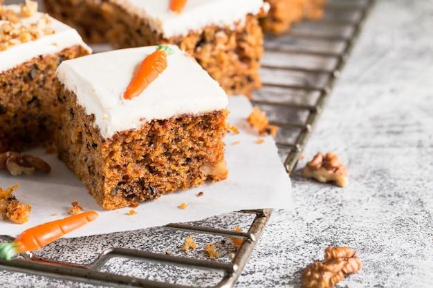 Pedaços de bolo de cenoura com nozes com creme de confeiteiro sobre um fundo claro. Foto Premium