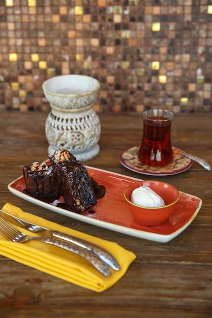 Pedaços de brownie com sorvete de baunilha, servidos com chá preto Foto gratuita