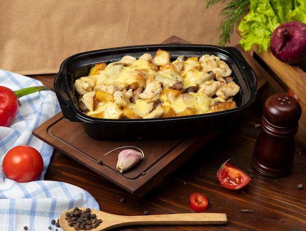 Pedaços de carne assada grelhada e fatias de batata em creme derretido queijo, molho de manteiga takeaway Foto gratuita