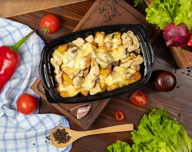 Pedaços de carne assada grelhada e fatias de batata em queijo creme derretido Foto gratuita